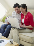 Couple With Laptop And Bills On Sofa Royalty Free Stock Images