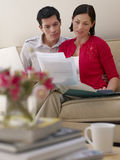 Couple With Laptop And Bills On Sofa Stock Images