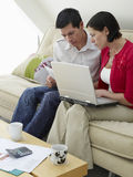 Couple With Laptop And Bills On Sofa Stock Image