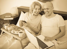 Couple with laptop during breakfast in bed stock photo