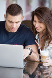 Couple with laptop at a cafe Stock Images