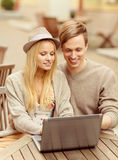 Couple with laptop in cafe Stock Images