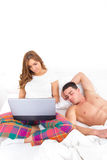 Couple with laptop computer in bed Stock Photos