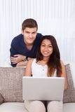 Couple With Laptop In Living Room Stock Photography