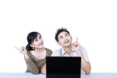 Couple with laptop looking up isolated Royalty Free Stock Photography