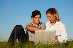 Couple with laptop on meadow Stock Image