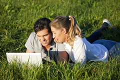 Couple with laptop on meadow. Young couple with a laptop computer surfing the internet outdoors on a meadow in beautiful yellow evening light Royalty Free Stock Photo