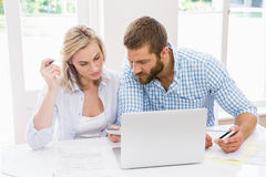 Couple with laptop and mobile phones discussing on bills. At home Royalty Free Stock Photo