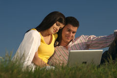 Couple with laptop in nature Stock Photo