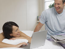 Couple With Laptop And Newspaper In Bed Royalty Free Stock Image