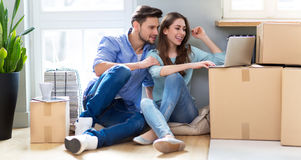 Couple with laptop next to moving boxes Royalty Free Stock Image