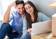 Couple with laptop next to moving boxes Stock Photos