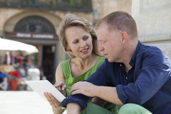 Couple with laptop outdoors Stock Image