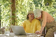 Couple with laptop outdoors Stock Photo