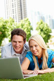 Couple on laptop in park Stock Photography