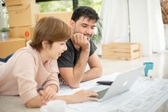 Couple with laptop planning their new moving house. Happy young couple with laptop and blueprints planning their new moving house royalty free stock photos