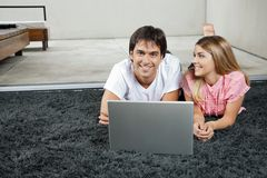 Couple With Laptop On Rug Royalty Free Stock Photos