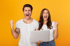 Couple with laptop shouting and clenching fists like winners. Over yellow background royalty free stock photos