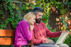 Couple with laptop sit bench in park nature background. Surfing internet together. Family surfing internet for royalty free stock image
