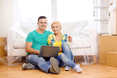 Couple with laptop sitting on floor in new house Stock Photography