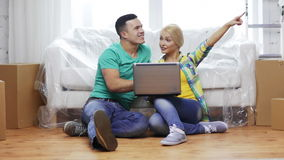 Couple with laptop sitting on floor in new house stock video footage