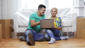 Couple with laptop sitting on floor in new house. Moving, home, technology and couple concept - smiling couple with laptop sitting on floor in new house stock footage