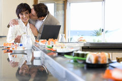 Couple with laptop in sushi bar, man kissing woman. Couple with laptop in sushi bar, men kissing woman Stock Photography
