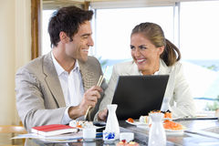 Couple with laptop in sushi bar, smiling at each other Stock Image