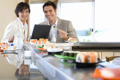 Couple with laptop in sushi bar, smiling, portrait Royalty Free Stock Images