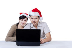 Couple with laptop and wearing christmas hat Royalty Free Stock Images