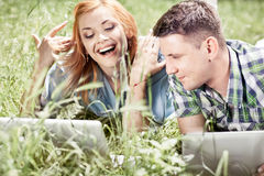 Couple with laptop. Young attractive couple lying on the grass, looking at laptop and smiling Royalty Free Stock Photos