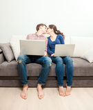 Couple with laptops kissing on couch at living room Royalty Free Stock Photography