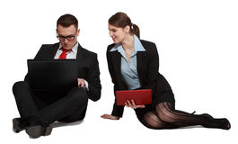 Couple on Laptops. Young business couple sharing one anothers work on their laptops while sitting against a white background Stock Photography