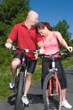 Couple Laughing while on Bicycles - vertical Royalty Free Stock Photos