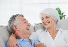 Couple laughing and chatting on a couch Royalty Free Stock Photo