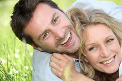 Couple laughing on the grass. Stock Photo