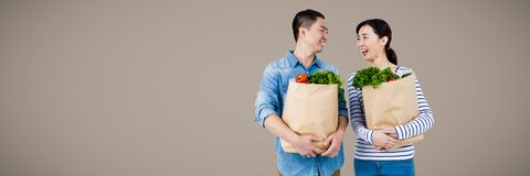 Couple laughing with grocery bags against brown background Stock Photo