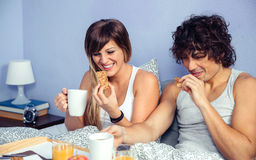 Couple laughing and having breakfast in bed at Stock Image