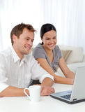 Couple laughing while looking at the laptop Stock Image