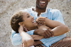 Couple laughing, man embracing woman, close-up Stock Photo