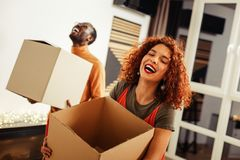 Couple laughing out loud while caring boxes with their clothes. Laughing out loud. Cheerful couple laughing out loud while caring boxes with their clothes royalty free stock images
