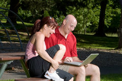 Couple Laughing at the Park - Horizontal. Couple lovingly sitting on a picnic table smiling and laughing together. The man is holding a laptop computer Stock Photography