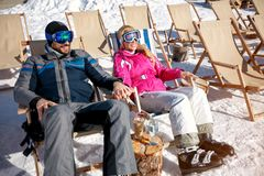 Couple laughing and relax in sunbed at mountains in winter. Happy couple laughing and relax in sunbed at mountains in winter Stock Images
