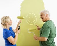 Couple laughing at smiley face painting. stock photos