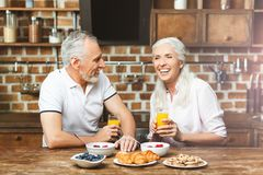 Couple laughing together while having breakfast stock images