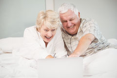 Couple laughing while using laptop in bed Stock Images
