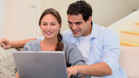 Couple laughing while using laptop stock video footage