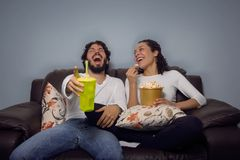 Couple is laughing and watching movie. Fun at home, leisure. Happy couple is laughing. Eating popcorn and drinking soda. Watching movie and series. They are stock images