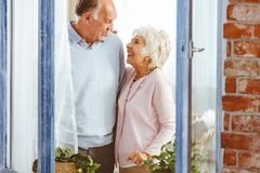 Couple laughing by the window. Senior happy couple laughing by the window at home Stock Photography