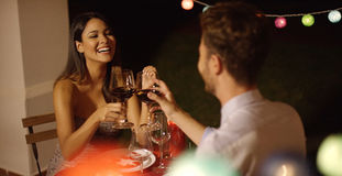 Couple laughs as they raise their wine glasses Stock Image